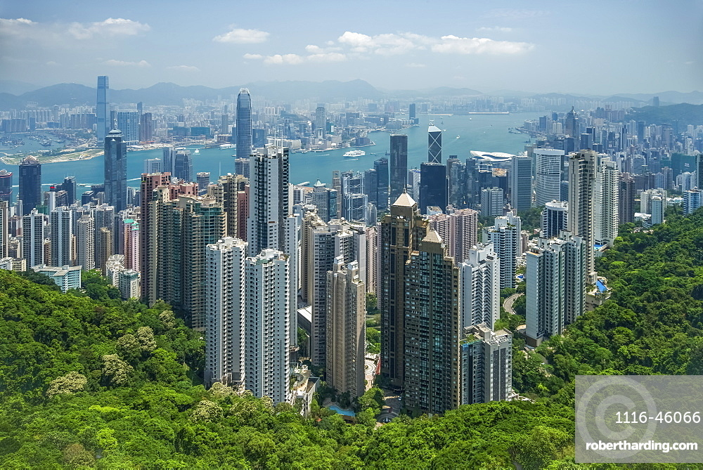 View Of Victoria Harbour Viewed From Victoria Peak, Showing Hundreds Of Skyscrapers Nestled Next To A Wooded Hillside, Hong Kong, China