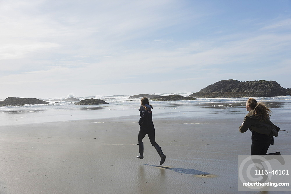 Teenage Girls Running On A Wet Beach At The Coast, Vancouver Island, Tofino, British Columbia, Canada