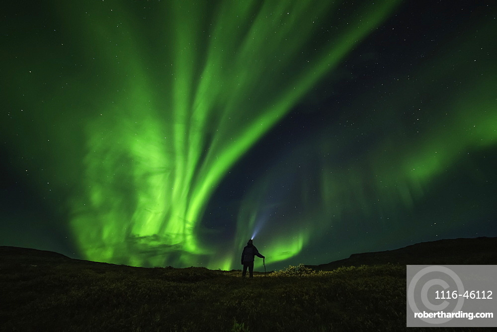 Man Standing Under The Northern Lights, Near Keno, Yukon, Canada