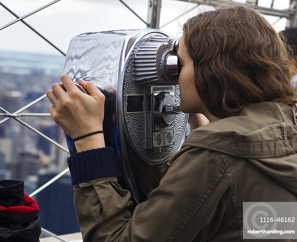 A Young Woman Looks Through Binoculars On The Observation Deck Of The Empire State Building To A View Of The Cityscape Of New York City, New York City, New York, United States Of America