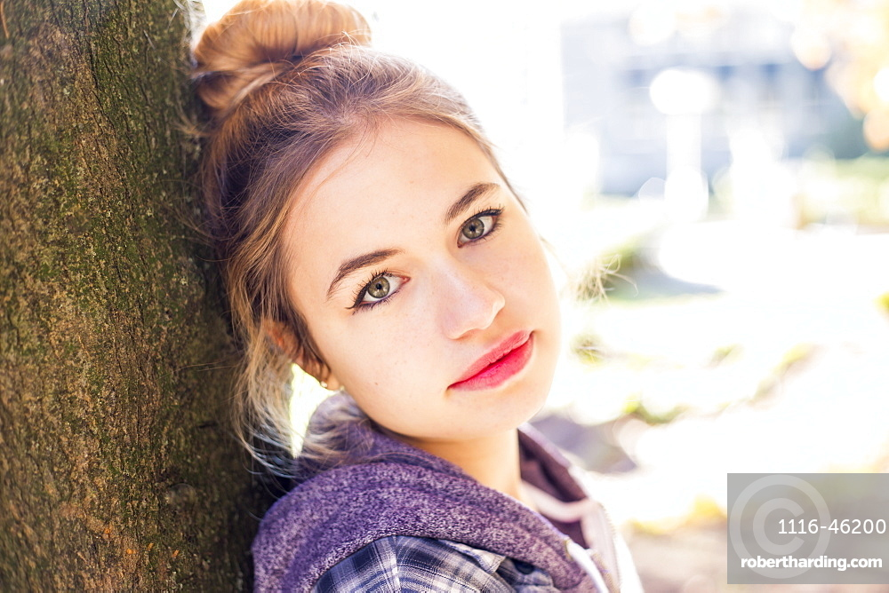 A Pretty Young Teenage Girl Looks Into The Camera With A Shy, Unconfident Look As She Leans On A Tree, New Westminster, British Columbia, Canada