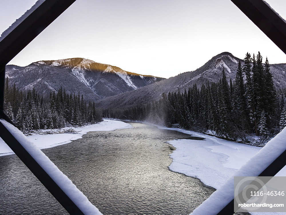 A Landscape With Snow Along The Shoreline Of A Lake And A Mountain Range Viewed Through A Diamond Shaped Window Frame, British Columbia, Canada