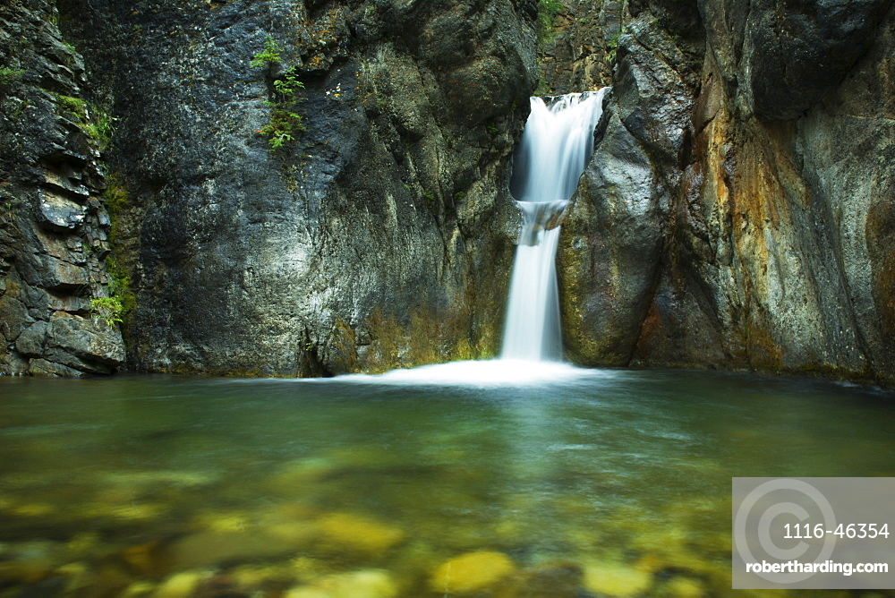 A Double Waterfall Drops Into Green Water In A Dark Canyon, Kananaskis Country, Alberta, Canada