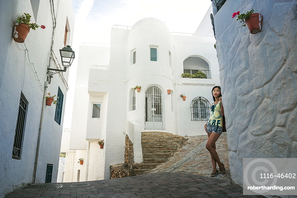 A Chinese Young Woman Standing Against A White Residential Building In Mojacar's Downtown, Mojacar, Almeria, Spain