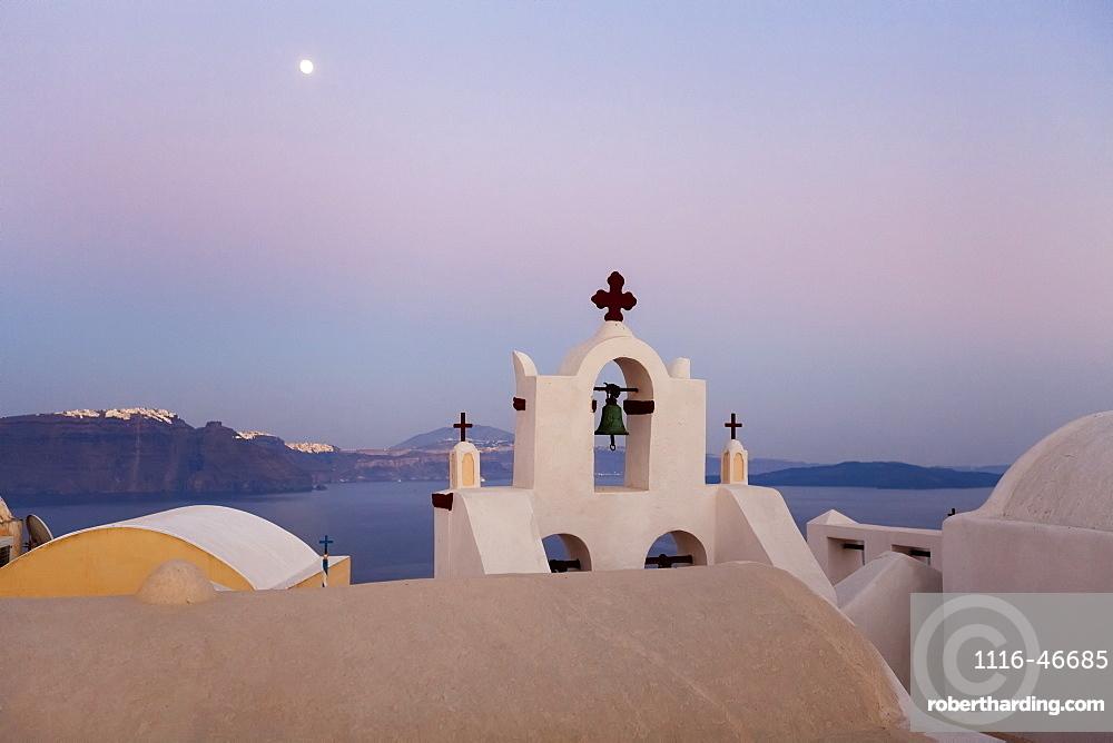 Orthodox Church With Bell And A Moon High In The Sky At Dusk, Oia, Santorini, Greece