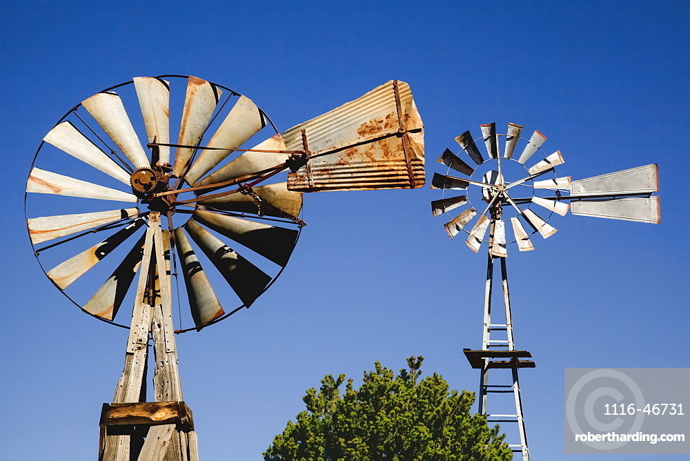 Close Up View Of Two Old Windmills Standing In The Yard Of A Farm, Quemado, New Mexico, United States Of America