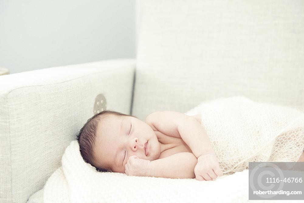 Newborn Baby Girl Asleep On Rocking Chair With Hand Nestled Up Near Face, Toronto, Ontario, Canada