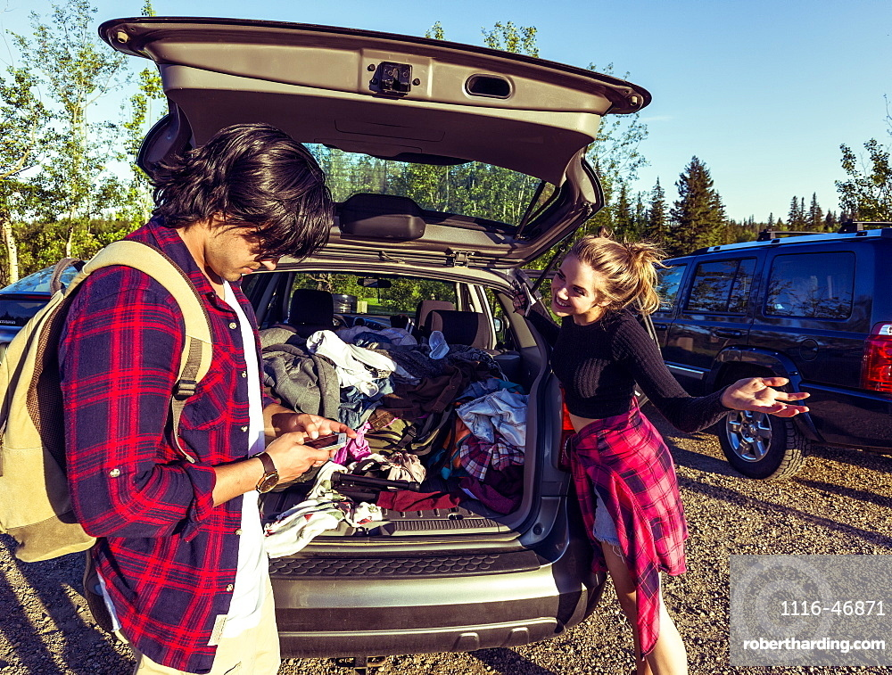 Young couple standing at the back of their packed vehicle with back door open and the young man in using his cell phone while the young woman waits impatiently, Edmonton, Alberta, Canada