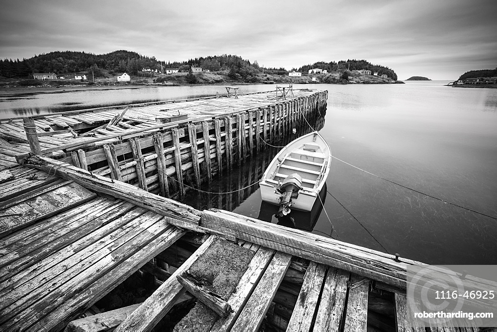 Black and white image of a boat tied to a wooden dock in a harbour along the Atlantic coast, Newfoundland, Canada