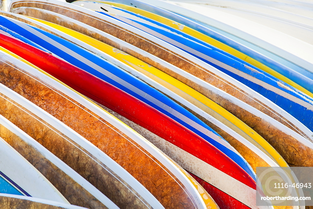 A stack of colourful longboard surfboards placed on the beach,, Waikiki, Oahu, Hawaii, United States of America