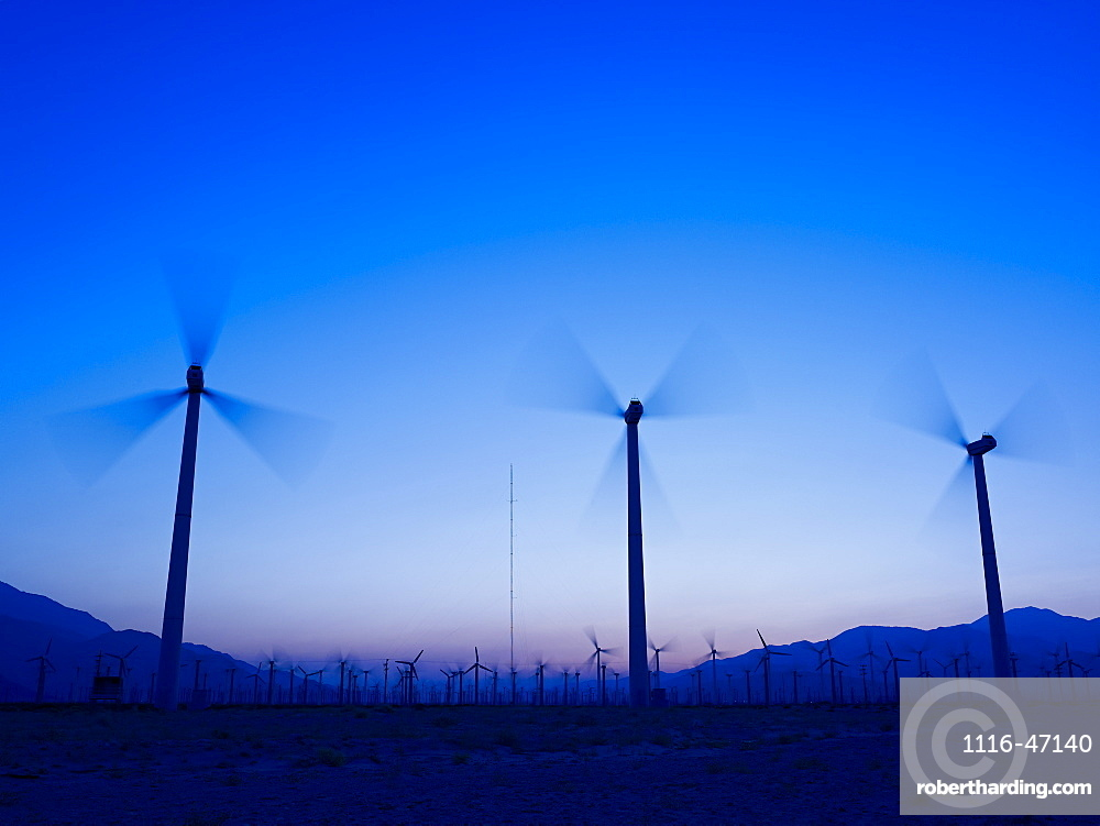 Silhouette Of Wind Turbines In A Field With A Mountain Range In The Distance At Sunset, Palm Springs, California, United States Of America