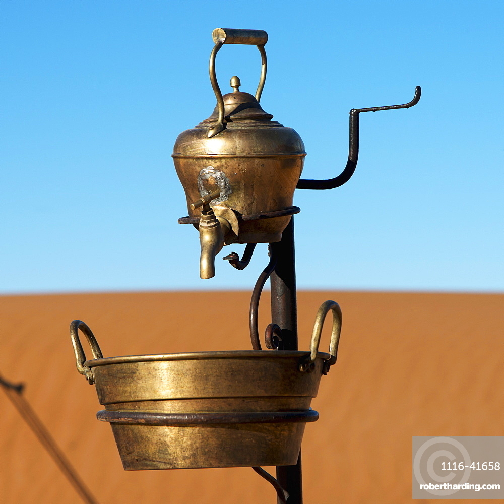 A metal teapot with a tap and bucket below with a sandy landscape and blue sky