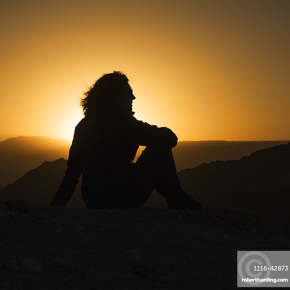 Silhouette Of A Woman Sitting With A View Of The Hilly Landscape Of Valle De La Luna At Sunset, San Pedro De Atacama, Antofagasta Region, Chile