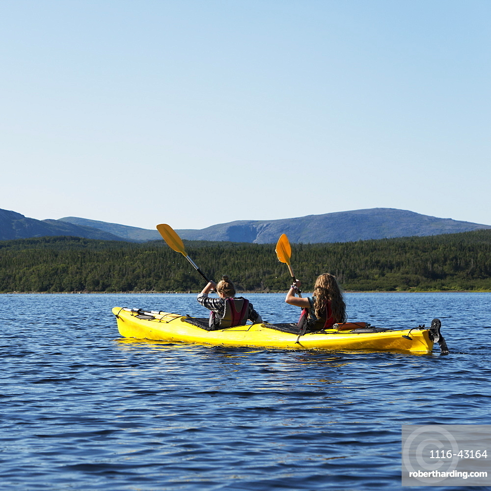 Two Young Women Kayaking In Gros Morne National Park, Trout River, Newfoundland, Canada