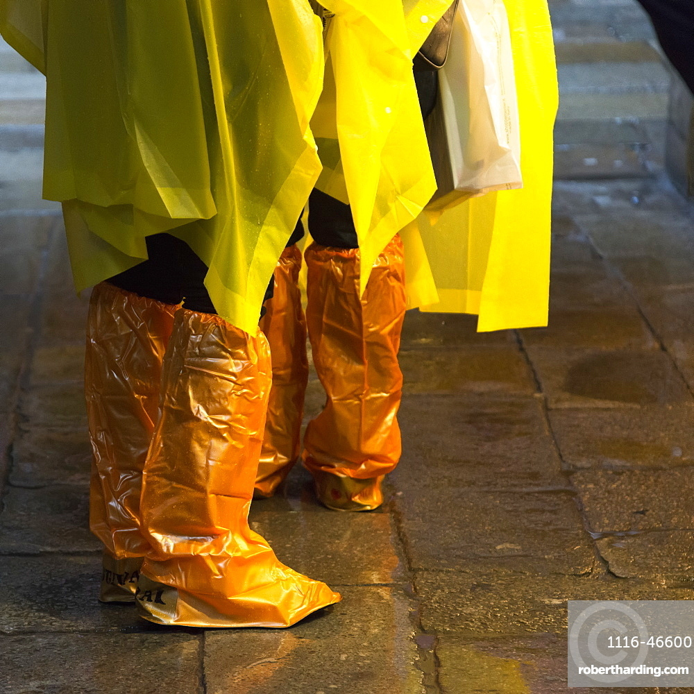 People Standing With Yellow Rain Ponchos And Footwear Covered In Orange Plastic Covers, Venice, Italy