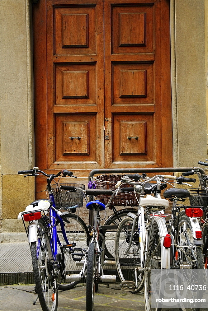 Florence, Italy, Bikes Parked At A Bike Rack Outside Wooden Doors