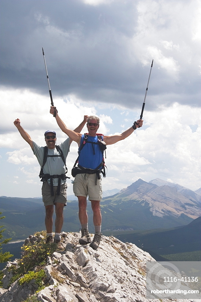 Two Men Cheering At The Top Of A Mountain