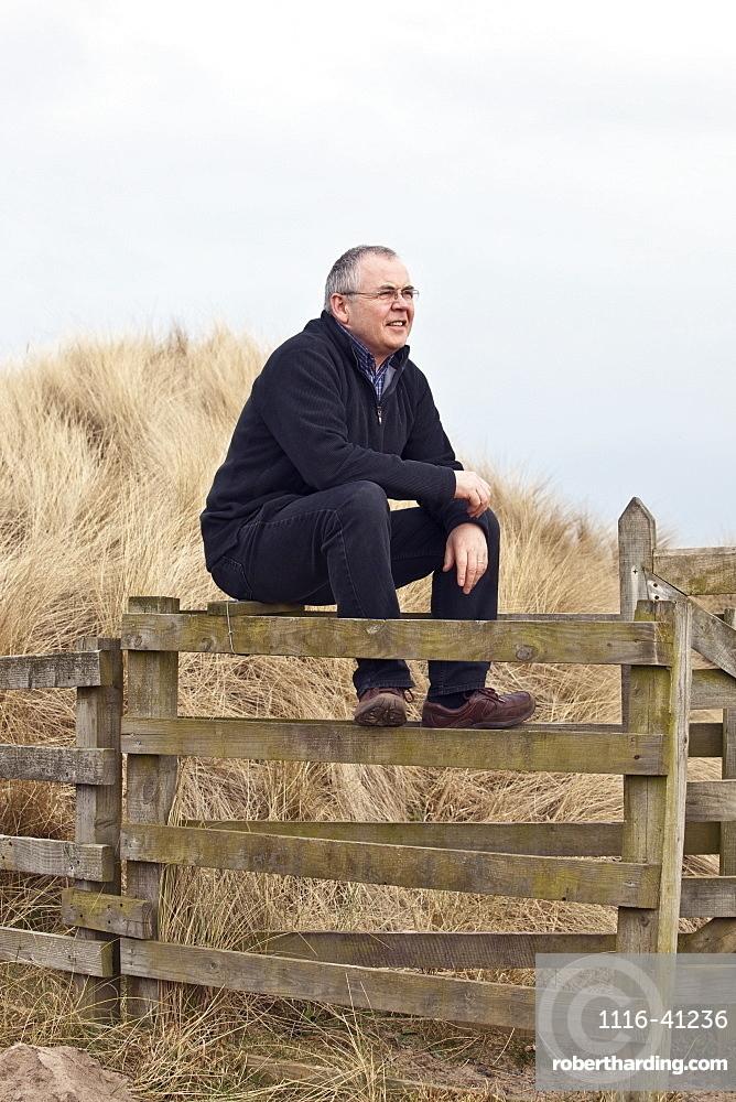 Northumberland, England, A Man Sitting On A Fence