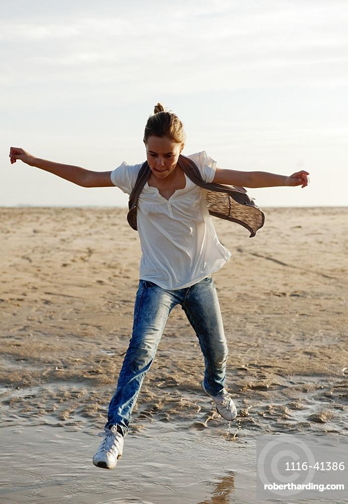 A Girl Jumps Over The Water On Los Lances Beach Along Costa De La Luz, Tarifa, Cadiz, Andalusia, Spain