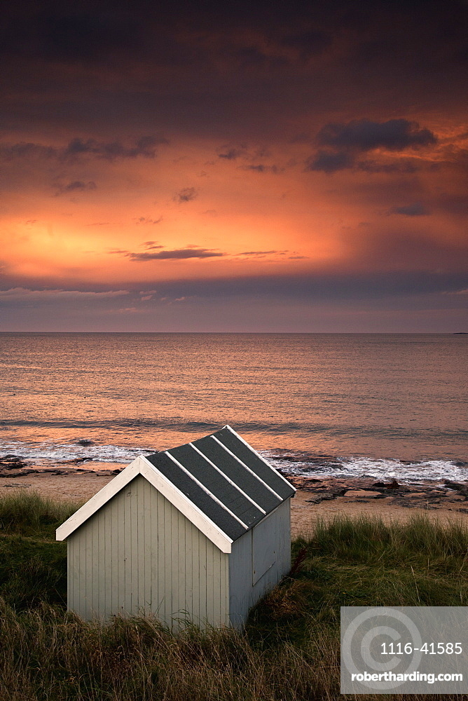 A Small Building Along The Water With A Pink Sky At Sunset, Bamburgh, Northumberland, England