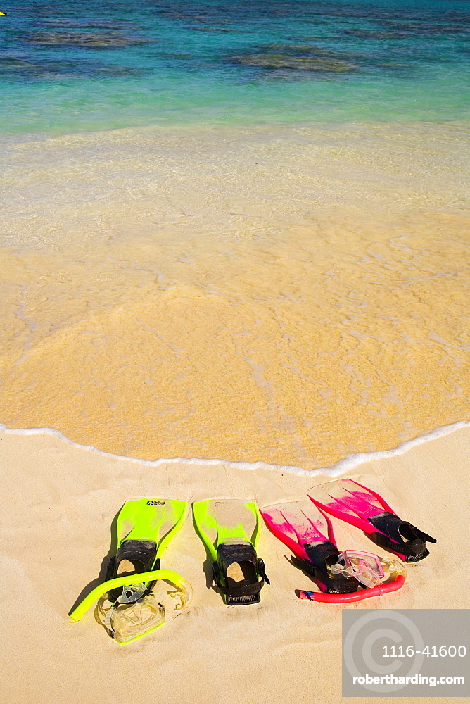 Two Sandy Snorkel Sets Rest At The Waters Edge On A Tropical Beach.