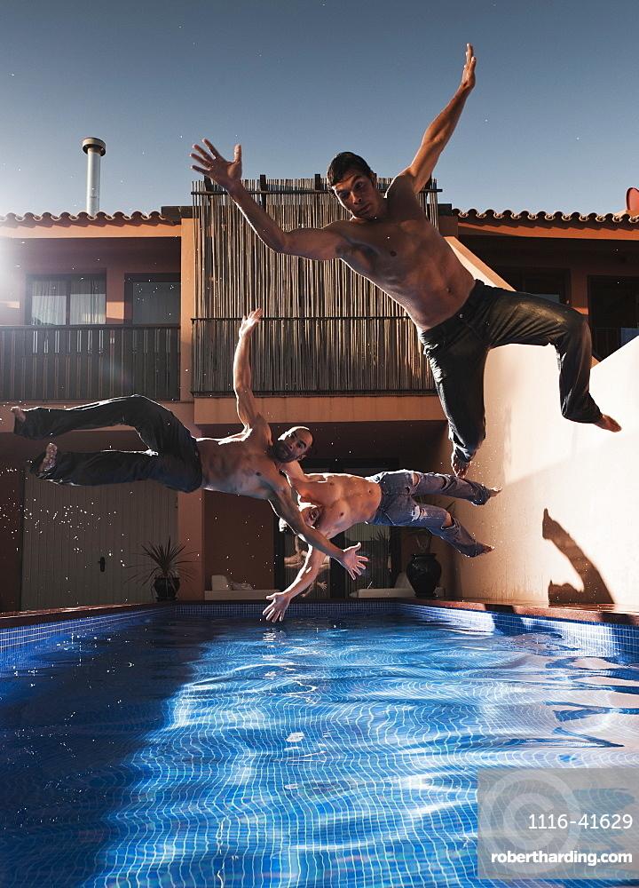Three Men Jumping Into A Pool Wearing Their Pants, Tarifa, Cadiz, Andalusia, Spain