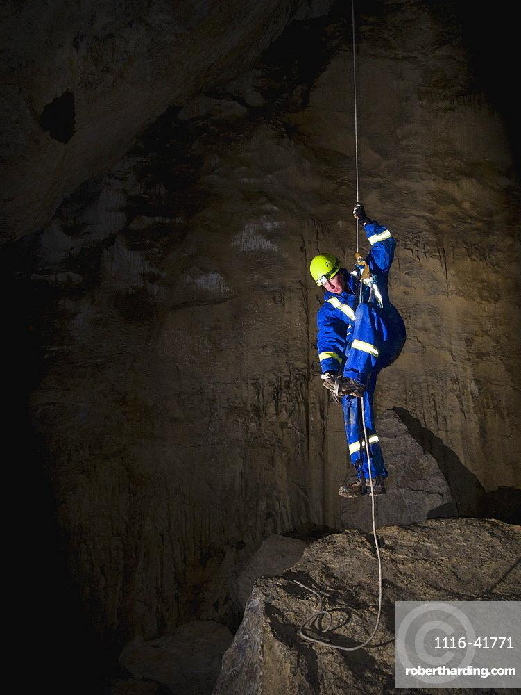 Male caver climbing a rope to exit a cave, Crowsnest pass alberta canada