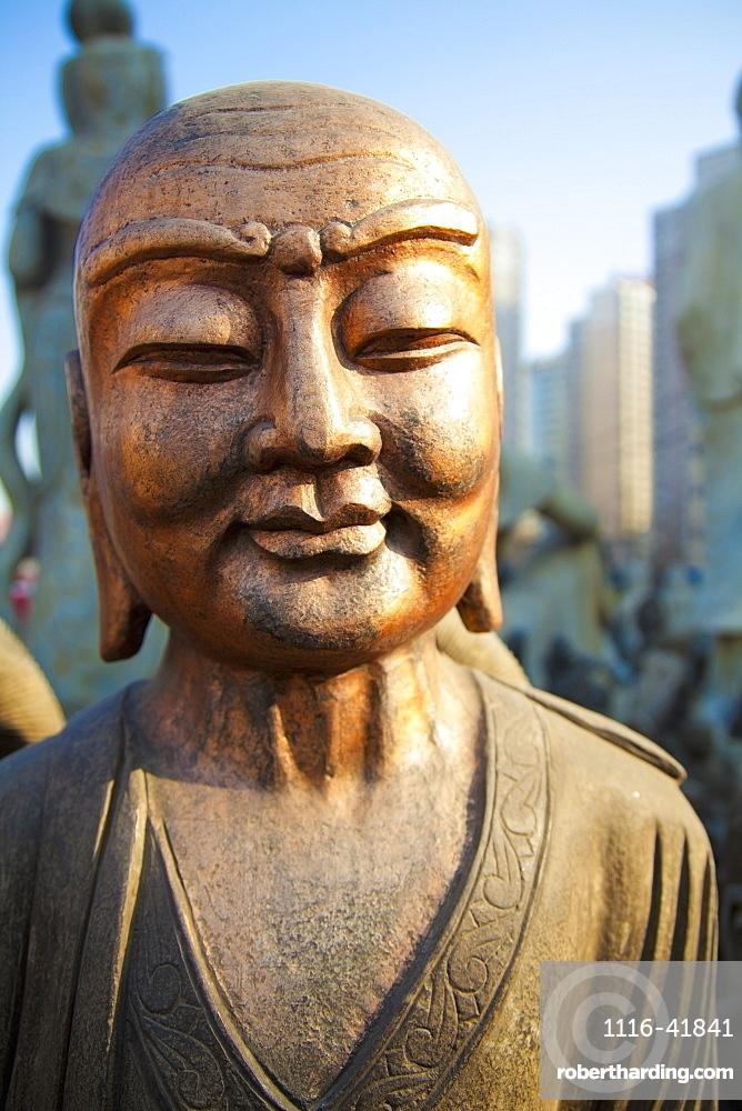 Bronze faced buddha statue glowing in warm light, Beijing china