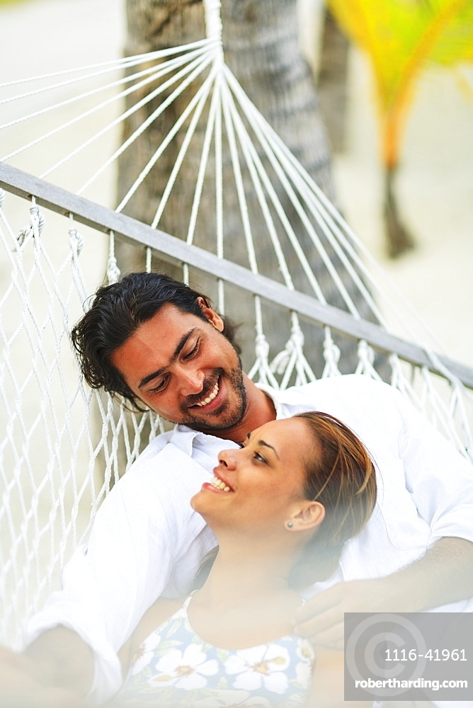 A man and woman in a hammock at the bora bora nui resort and spa, Bora bora island society islands french polynesia south pacific