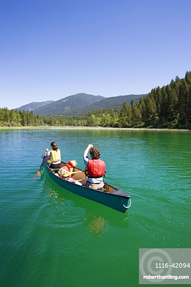 Young Family Canoeing On Loon Lake In The East Kootenays, British Columbia, Canada