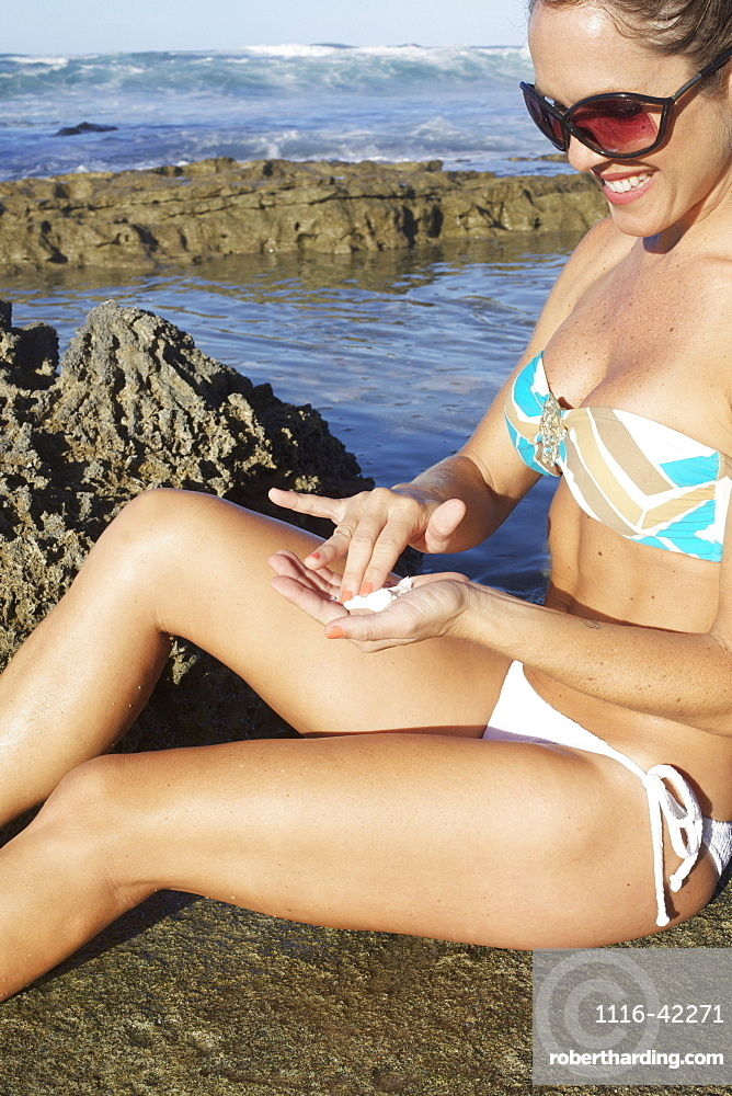 A Young Woman In A Bikini Sits On The Beach At The Water's Edge With Sunscreen Her Hand, Hawaii, United States Of America