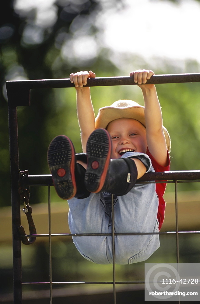 Agriculture - A young farm girl wearing a cowboy hat and rubber boots swings on a metal gate, hanging by her hands and legs and laughing / Northwest Missouri, USA.