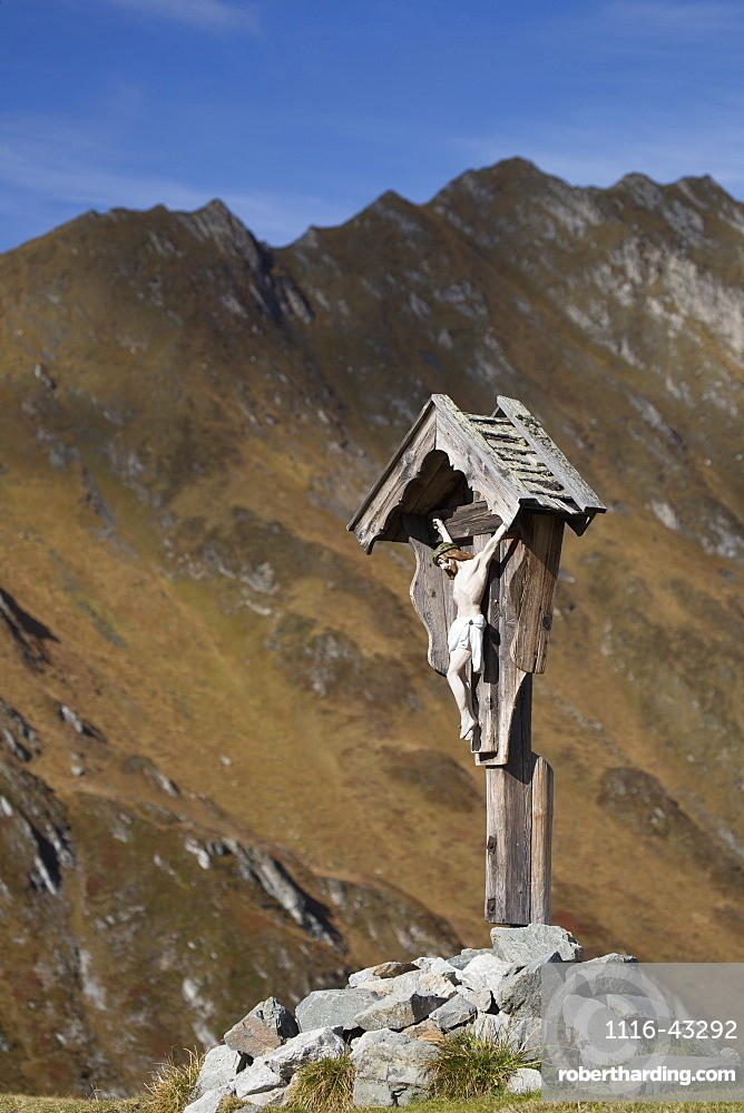 Wooden Crucifix Memorial On Grassy Slope With Mountain Range And Blue Sky In The Background, Hintertux, Austria