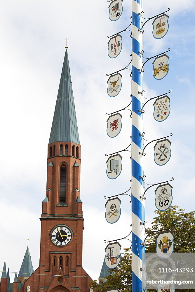 Close Up Of A Traditional Bavarian May Pole With Blue And White Stripes With Crests And A Church Steeple In The Background, Munich, Germany