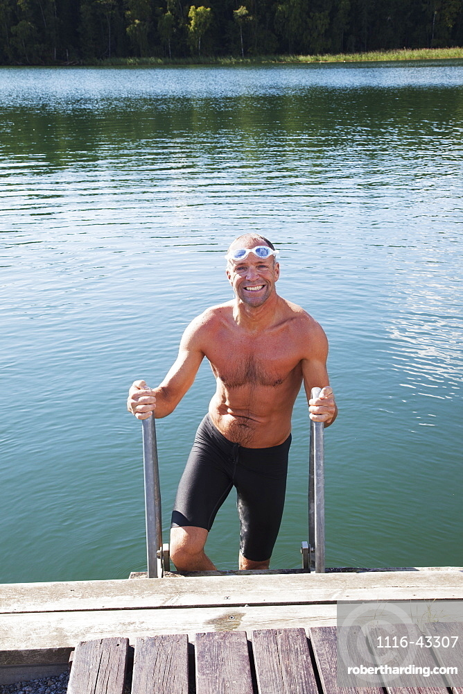 Man Getting Out Of The Water Onto A Dock, Morbylanga, Sweden