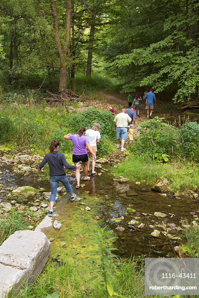 Family Crossing Bear Creek On Hiking Trail Leading To The Ice Cave At Bixby State Preserve, Near Edgewood, Iowa, United States Of America