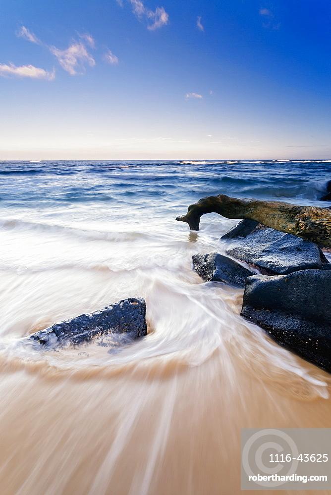 Surf Washing Up Around Driftwood And Rocks, Wailua, Kauai, Hawaii, United States Of America