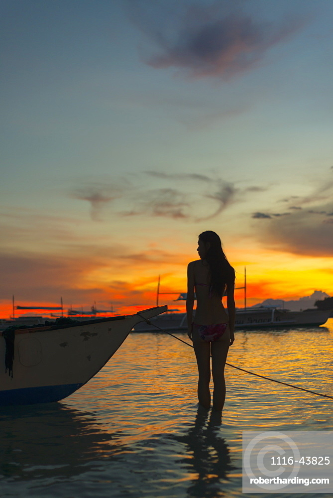A Young Woman Stands In The Shallow Water Beside A Boat At Alona Beach At Sunset, Panglao Island, Bohol, Philippines
