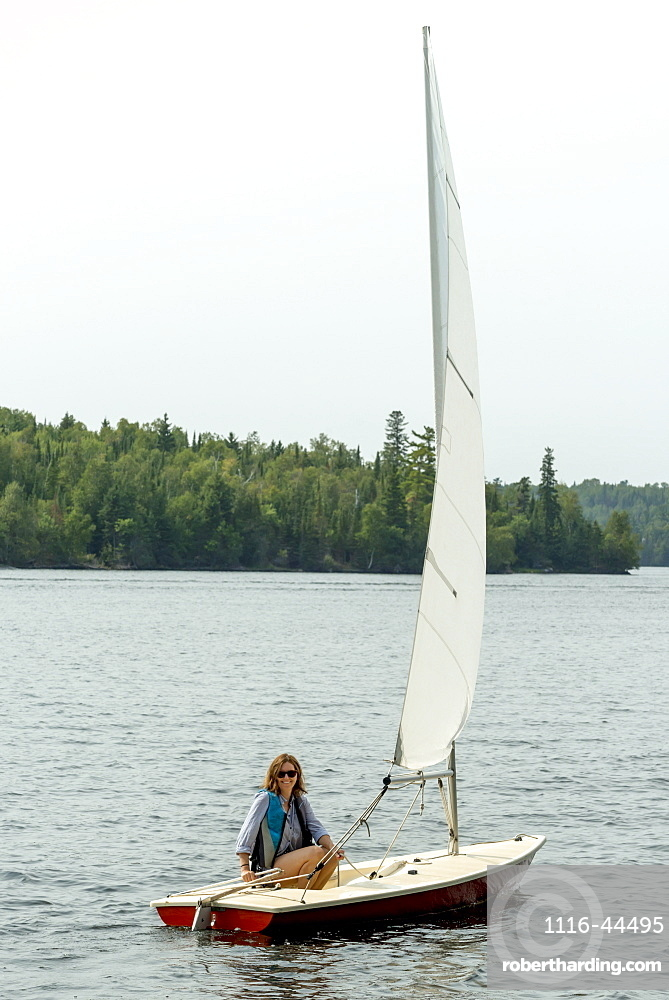 A Woman Sits On A Small Sailboat In A Lake, Ontario, Canada