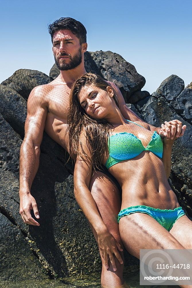 A Couple In Swimwear Leaning Against A Rock At The Coast, Tarifa, Cadiz, Andalusia, Spain