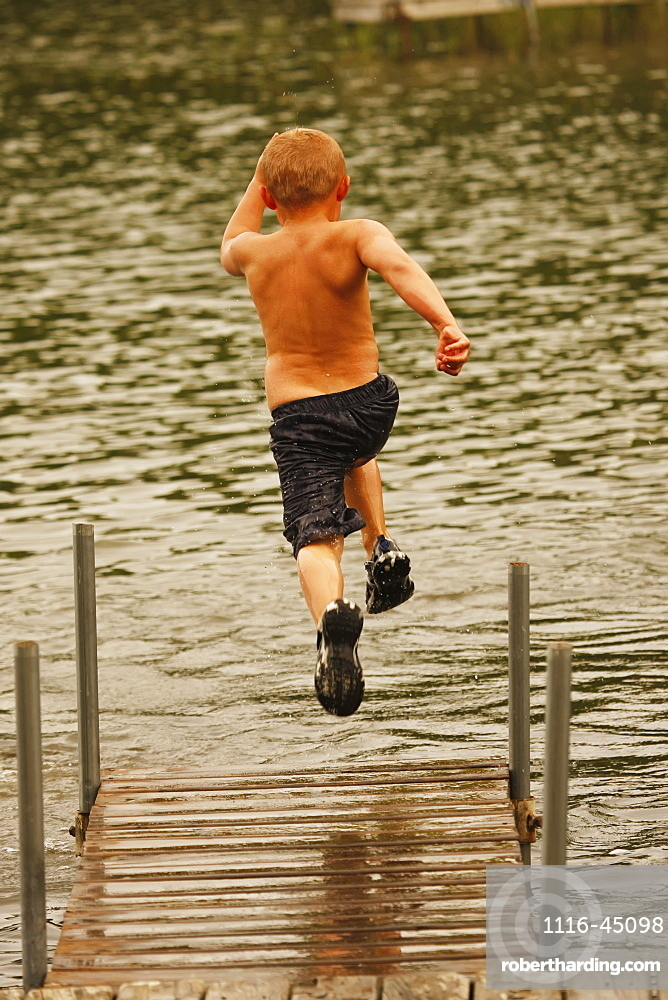 Boy Running And Jumping Off The Dock In A Lake