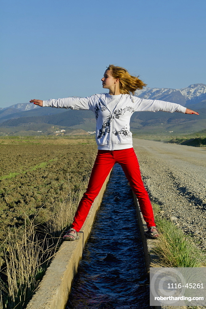 Teenage Girl Standing Over A Small Canal Of Water With Arms Outstretched, Andalusia, Spain