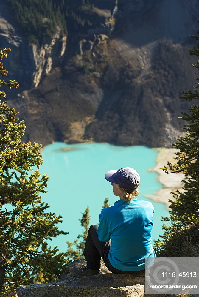 Female Hiker Sitting On Rock High Above Intense Blue Coloured Mountain Lake With Mountain Cliffs In The Background, Banff National Park, Alberta, Canada