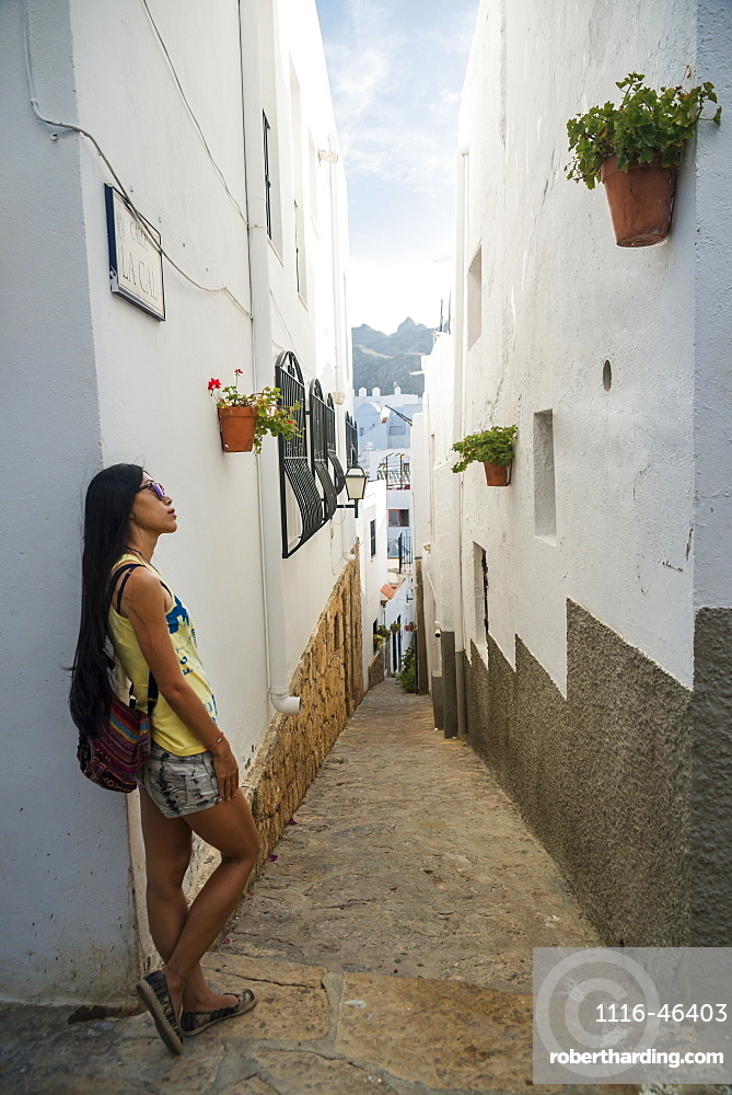 A Chinese Young Woman Standing Against A White Residential Building In A Narrow Street, Mojacar, Almeria, Spain