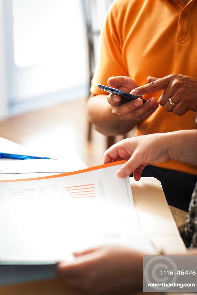Man And Woman With Documents And A Calculator, Regina, Saskatchewan, Canada