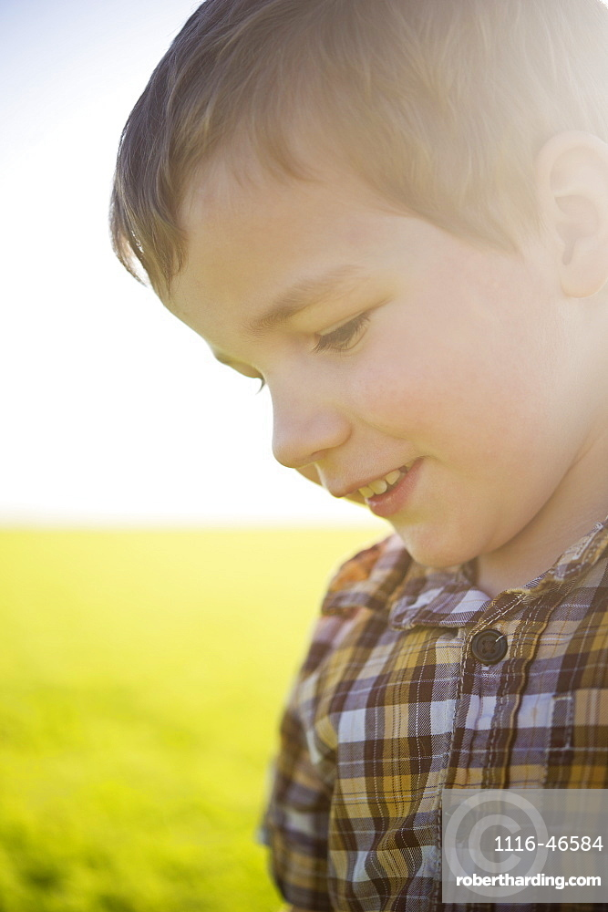 Young Boy's Profile With Sunlight Hitting His Face In A Farm Field, Saskatchewan, Canada