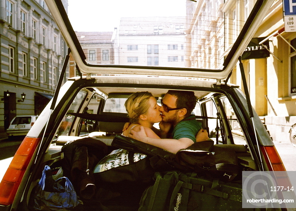 A man and woman kissing in the backseat of a car