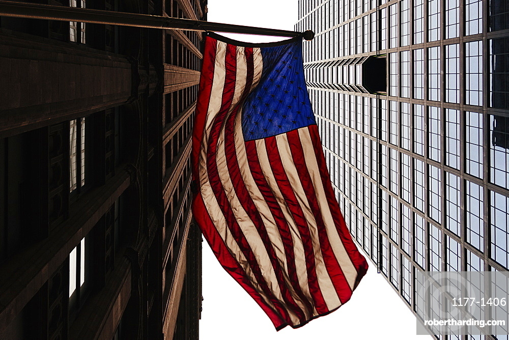 Low angle view of American flag and office buildings