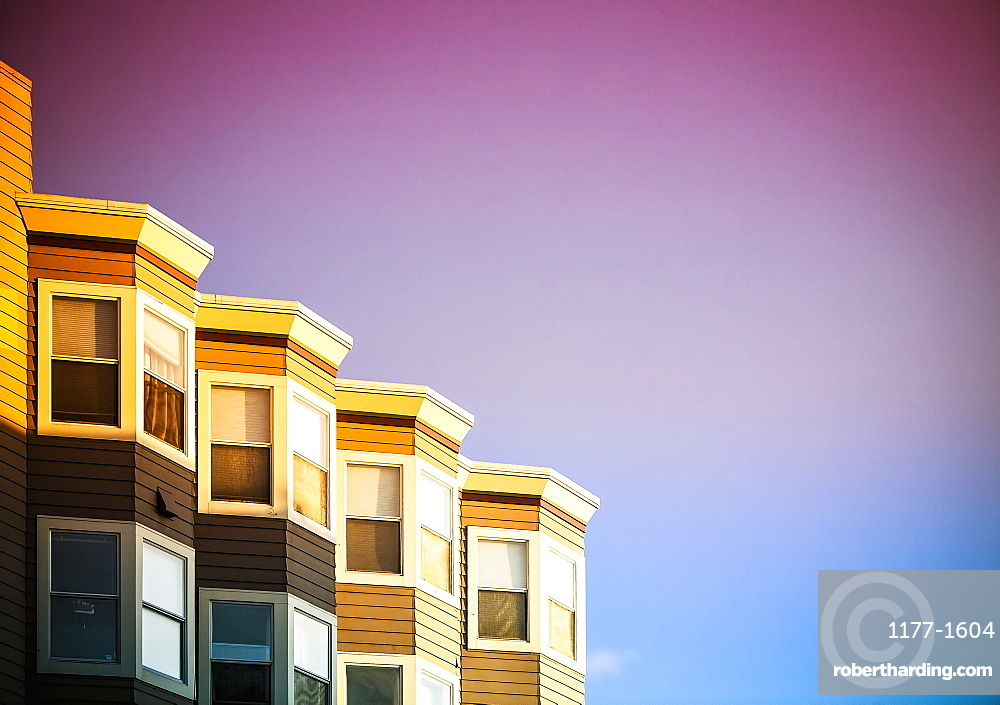 Low angle view of residential buildings against sky during sunset