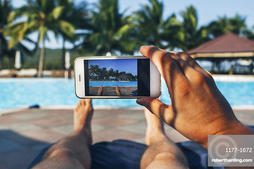 Low section of man photographing swimming pool in tourist resort